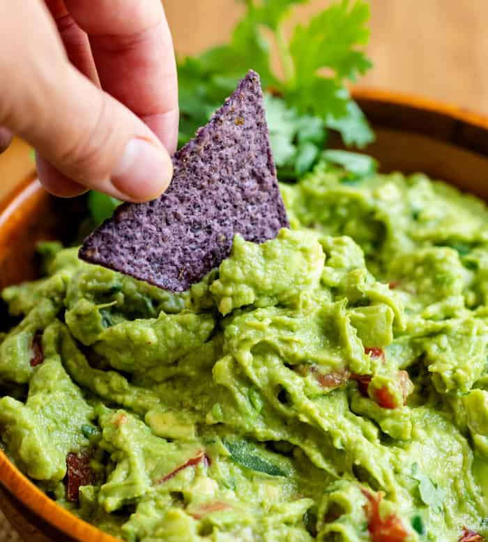 Close up view of a hand dipping a tortilla chip into a bowl of guacamole.
