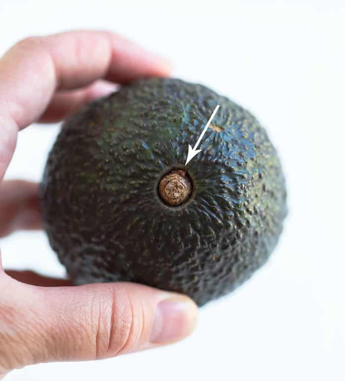 Close up shot of a hand holding an avocado with an arrow pointed at the pit.