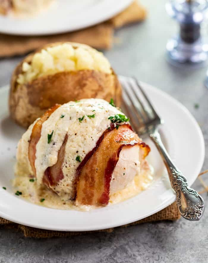 Bacon wrapped chicken topped with white sauce and parsley on a white plate with a baked potato in back.