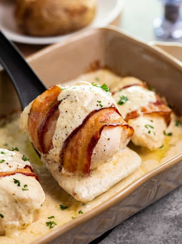 Black spatula picking up chicken wrapped in bacon with white sauce drizzled on top in a casserole dish.