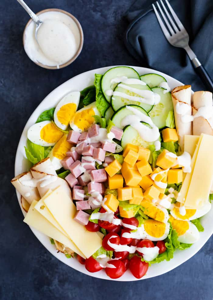 overhead view of a loaded, colorful chef salad on a white plate with a ramekin of ranch dressing and a fork next to it on a dark blue surface.