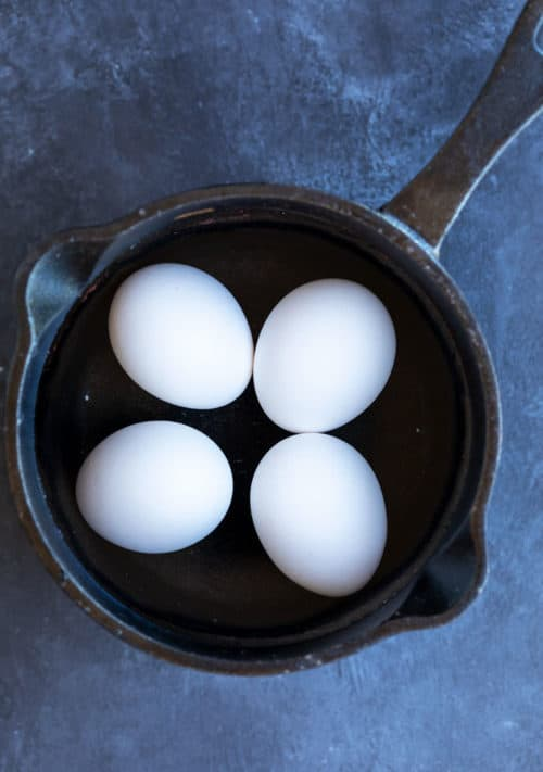 Overhead view of a cast iron pot filled with water and 4 hard boiled eggs on a dark blue surface.