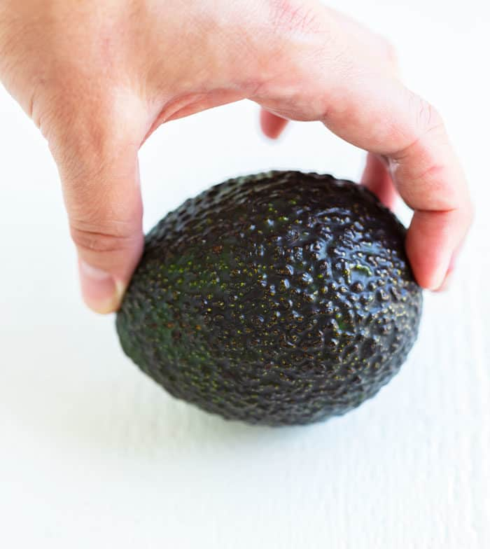 A hand holding each end of an avocado to test for ripeness.