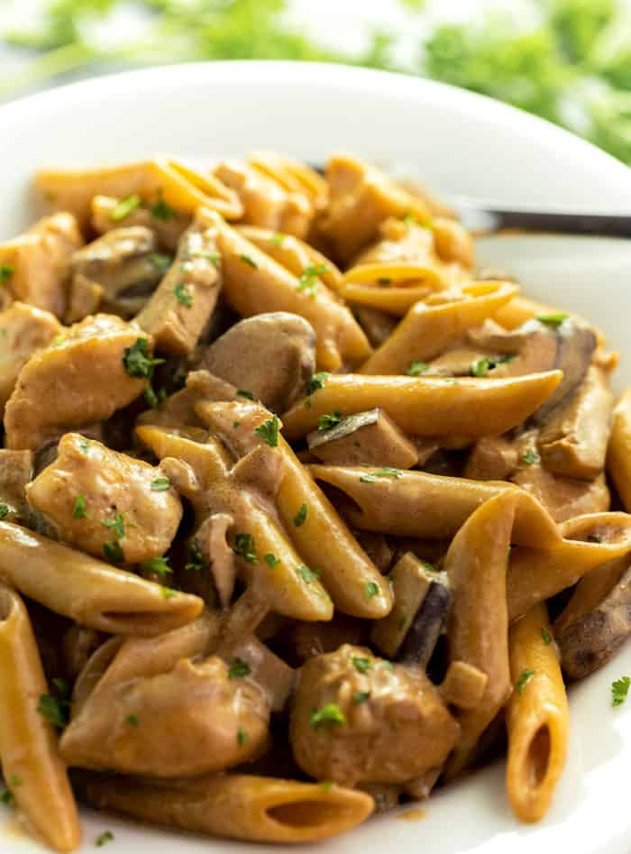Close up image of De Vinci Pasta on a white plate with mushrooms and fresh parsley on top