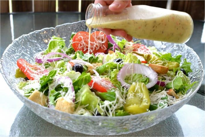 copycat olive garden salad dressing being poured over a large glass bowl filled with olive garden salad.
