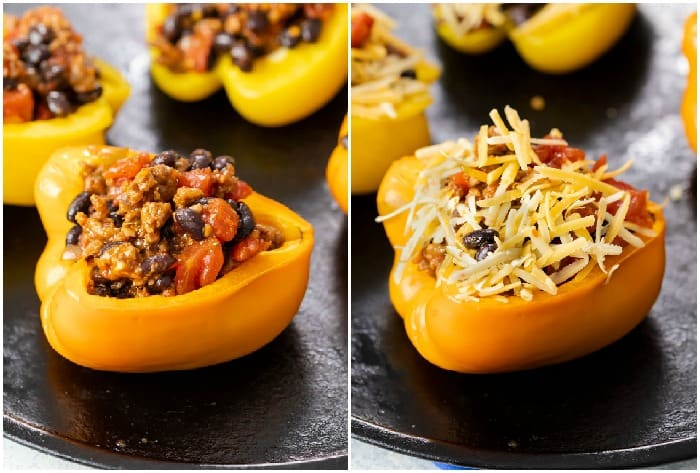 Bell peppers on a baking sheet filled with taco filling and topped with shredded cheese.