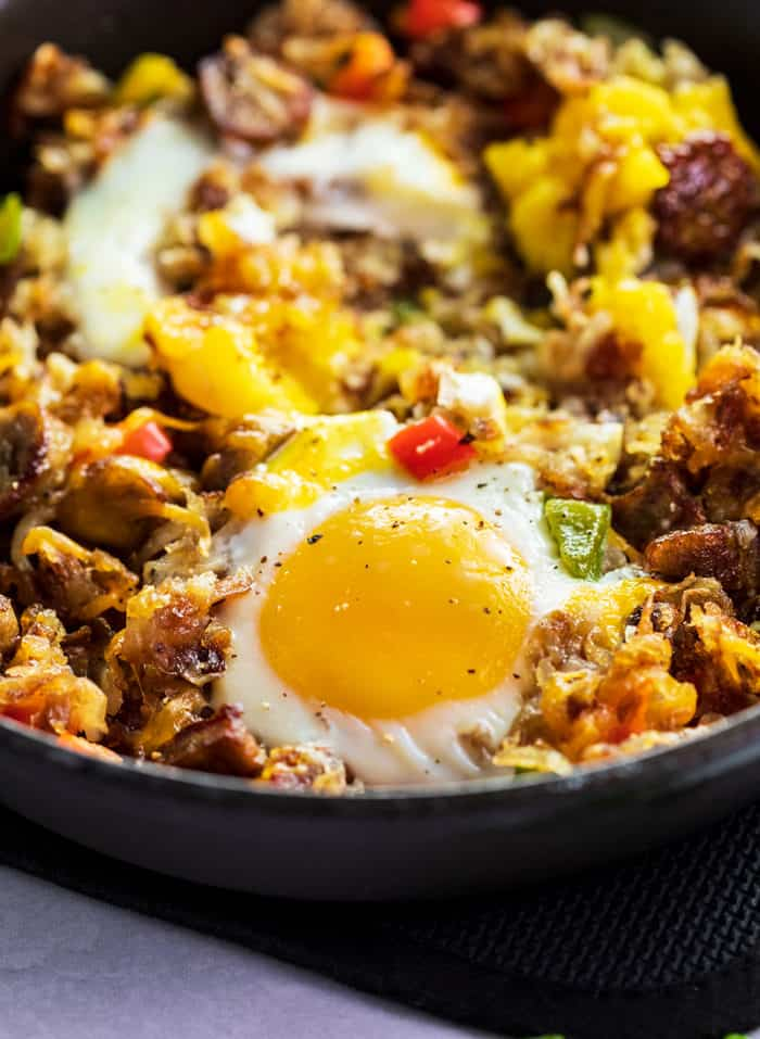 A close up shot of a baked egg in an iron skillet with hash, sausage, and bell peppers