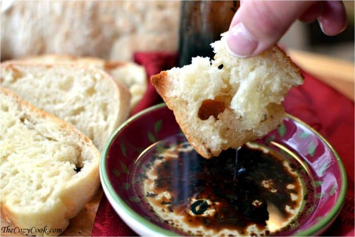 Hand Dipping Homemade Ciabatta bread in oil and balsamic.