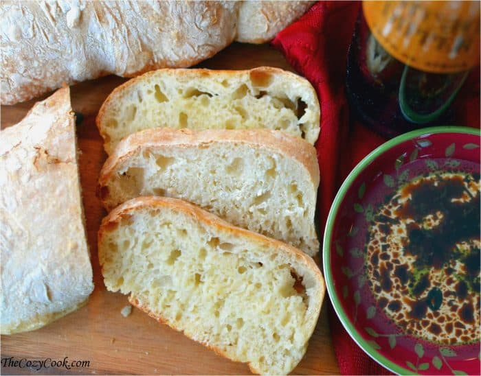 Slices of homemade ciabatta bread next to a dish of oil and balsamic for dipping.