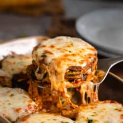 A stack of eggplant Parmesan topped with melted Mozzarella cheese being scooped up with a spatula.