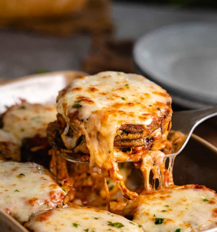 A spatula holding up warm, cheesy eggplant Parmesan.