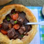A bowl topped with pastry filled with beef stew with a spoon in it.