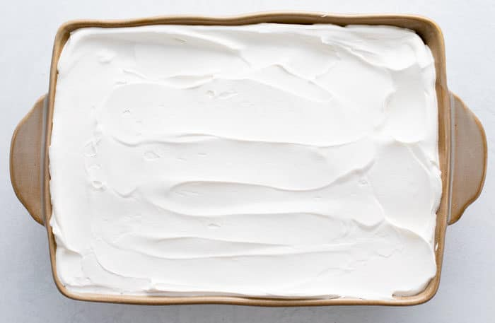 Overhead view of baking dish with whipped cream spread out inside of it.