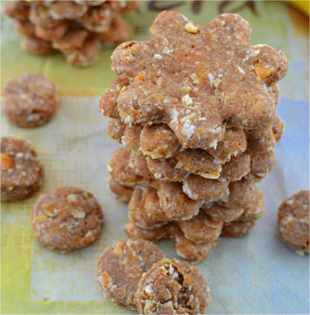 a stack of homemade dog treats in a flower shape with smaller round dog treats next to it.