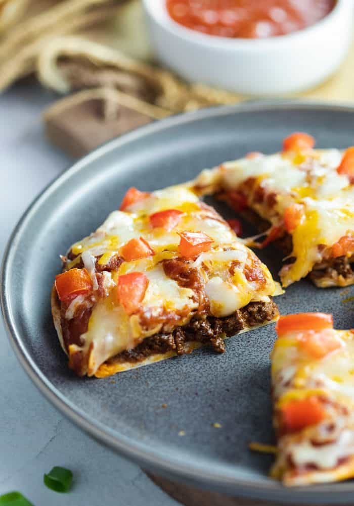 Slice of Taco Bell Mexican Pizza on a blue plate. Pizza is topped with melted cheese and tomatoes and filled with ground beef and refried beans.