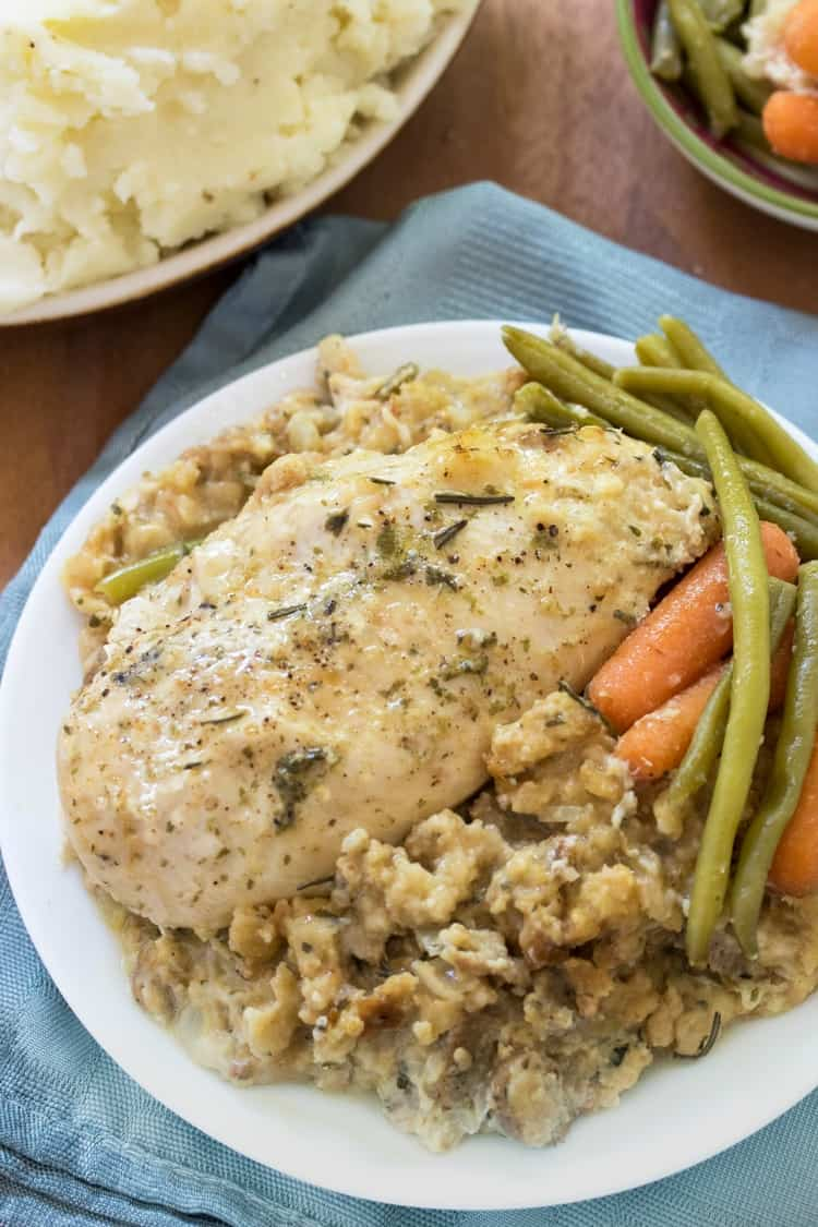 A cooked and seasoned chicken breast on top of moist stuffing on a white plate with green beans and carrots.