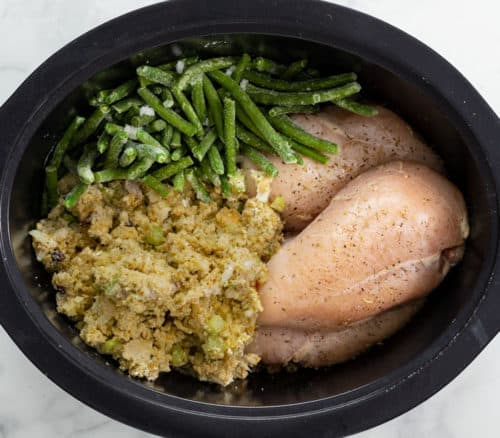 Uncooked stuffing, green beans, and chicken breasts in a crock pot.