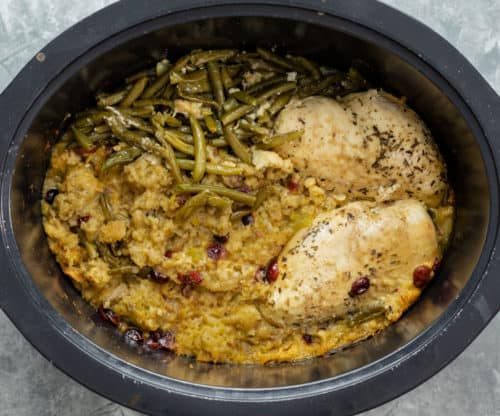 Crock Pot full of cooked stuffing, seasoned chicken, and green beans.