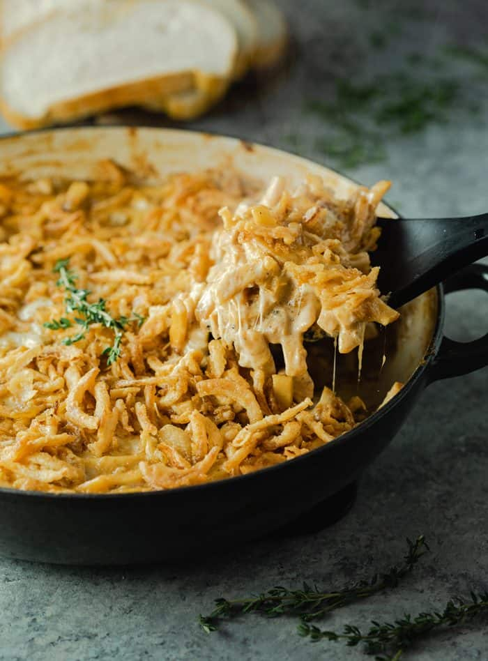 French onion noodle casserole in a large casserole dish with spatula pulling up the noodles