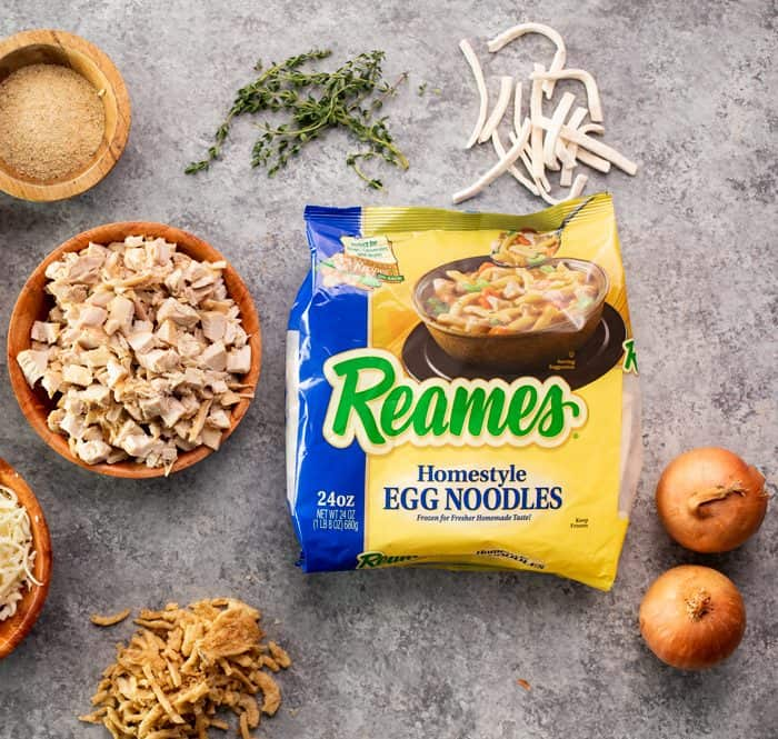 Yellow package of reames homestyle egg noodles on blue countertop next to other ingredients