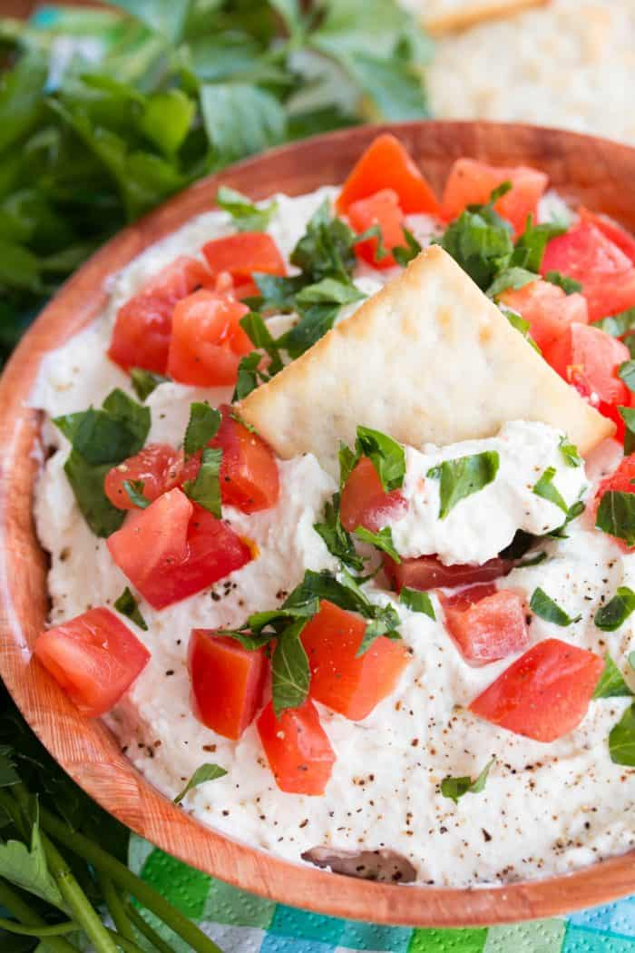 Chilled garlic feta dip topped with diced tomatoes with a cracker on top and parsley in the background.