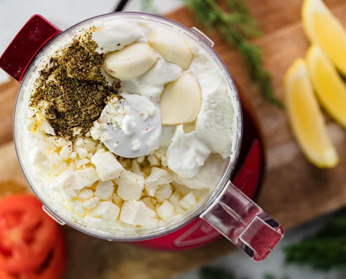 Food processor filled with feta cheese, garlic, cream cheese, and spices for garlic feta dip.