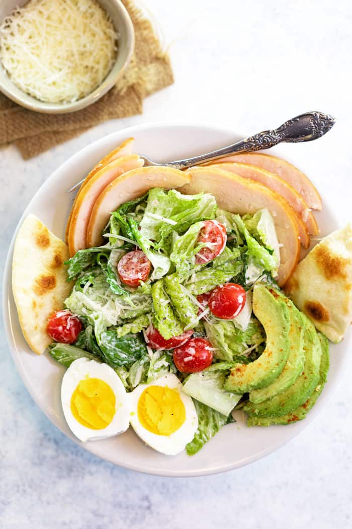 Overhead shot of Caesar Salad with cherry tomatoes, hard boiled eggs and sliced avocado.