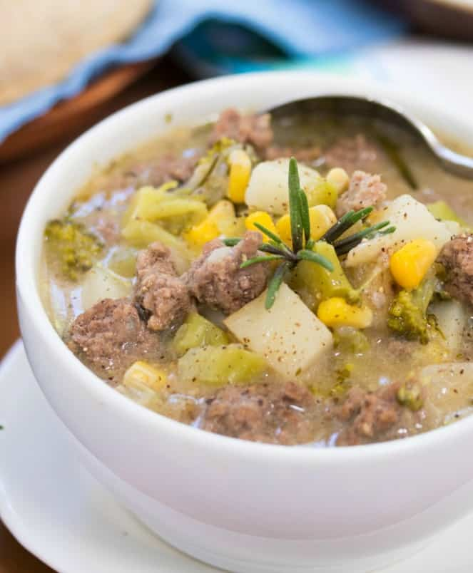 Close up shot of a white bowl filled with hamburger soup topped with rosemary.