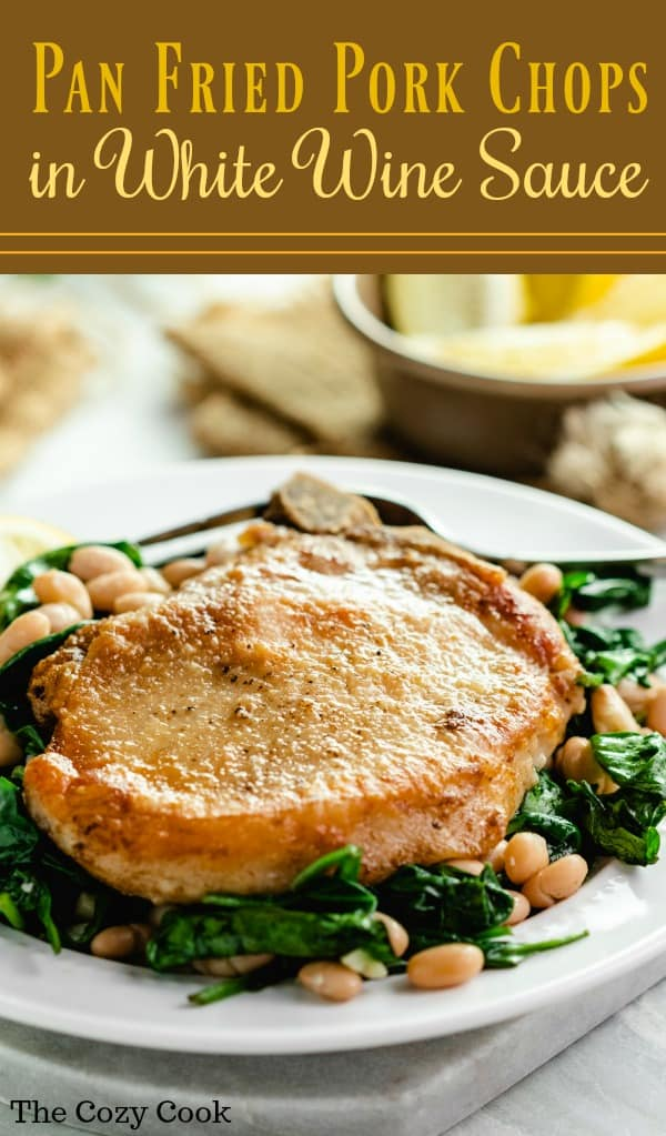 These mouth-watering Pork Chops are pan fried to golden perfection and are served with a simple garlic and white wine reduction over a bed of flavorful spinach and white beans.| The Cozy Cook | #porkchops #dinner