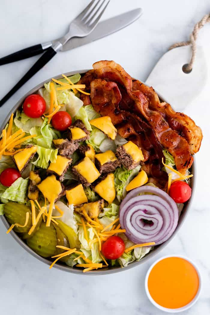 Overhead view of a big cheeseburger salad in a bowl on a white table with a fork, knife, and big mac sauce.