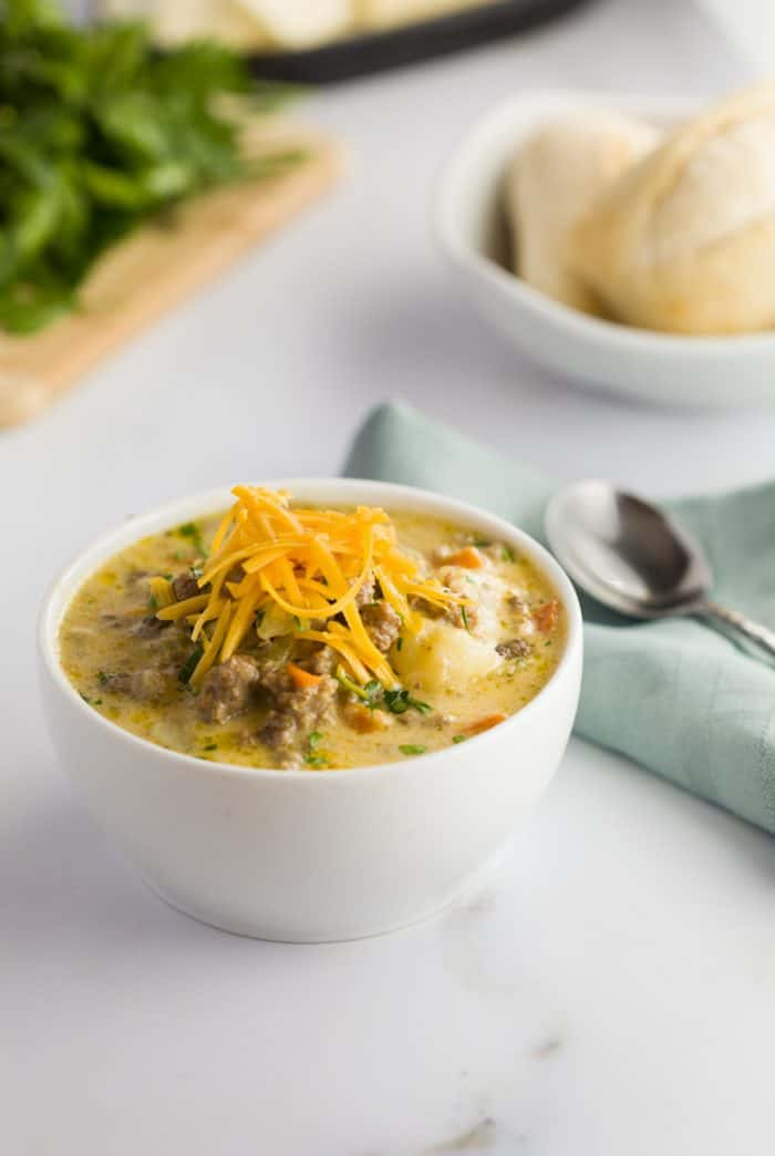 Slow Cooker Cheeseburger Soup in a white bowl on a white countertop with rolls in the background.