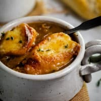 A mug of French Onion Soup topped with 2 slices of cheesy baguettes.