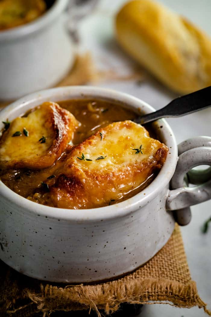 Two slices of baguette with melted cheese in a bowl of french onion soup  and thyme