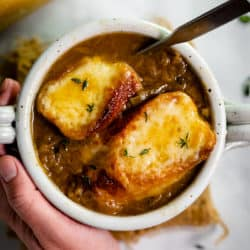 A mug filled with French Onion Soup topped with cheesy baguettes.
