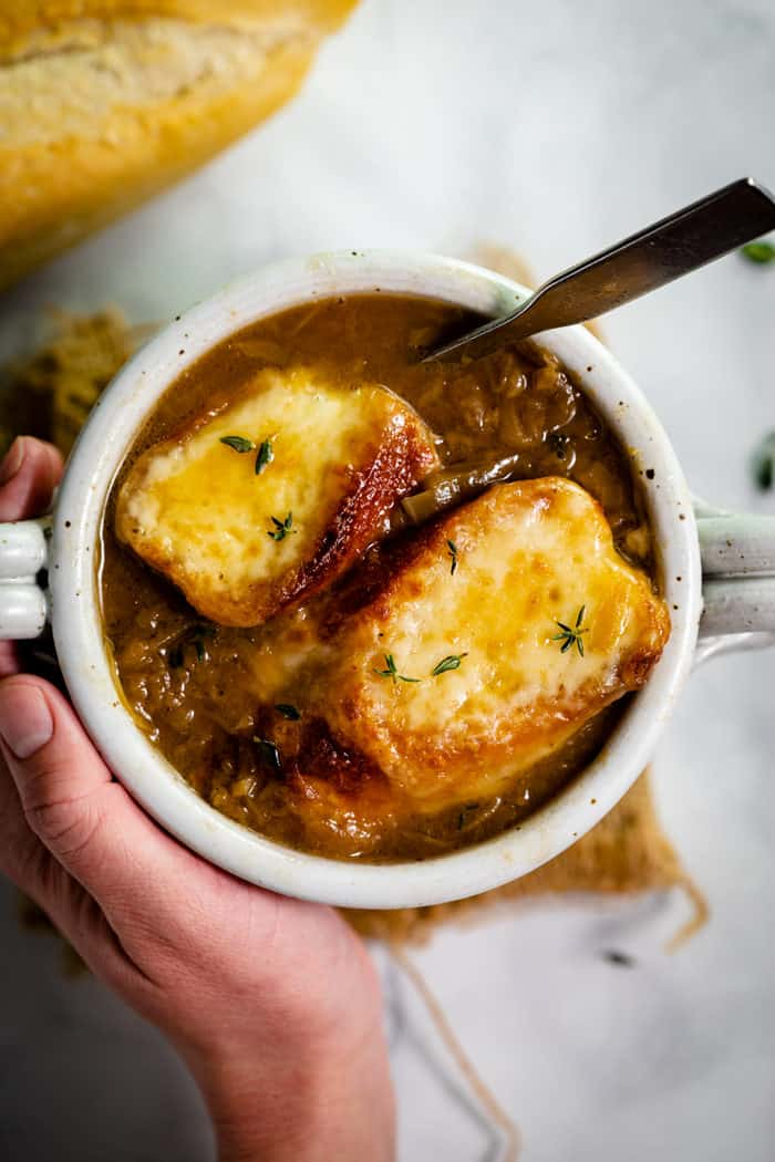 Overheat shot of a hand holding a white bowl filled with french onion soup topped with two cheesy baguettes.