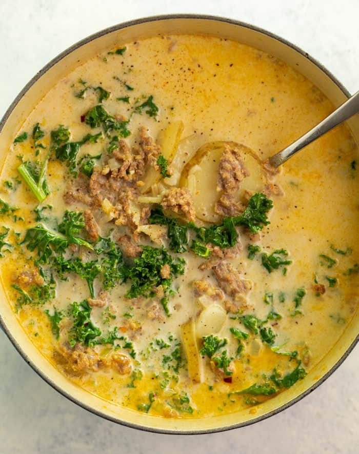 Soup pot filled with zuppa toscana soup with ladel in it. Creamy broth, kale, and sausage.