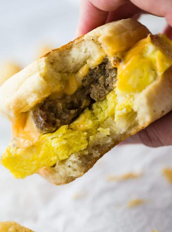 A close up view of a hand holding a sausage egg and cheese sandwich with a bite taken out of it.