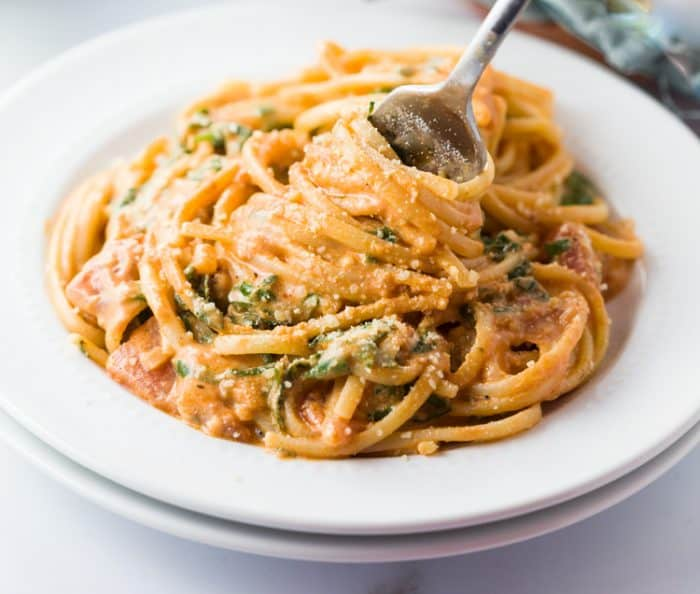 A white plate with a fork twirling up Creamy Tomato Spinach Pasta