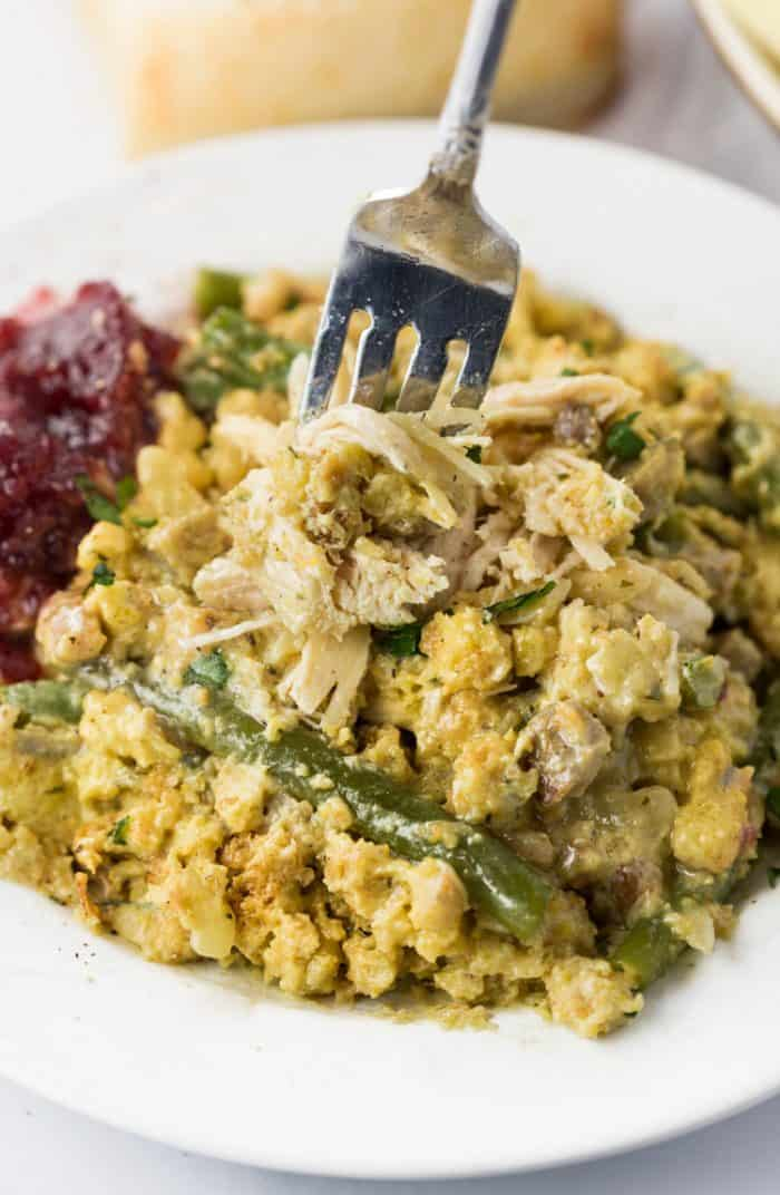 a fork full of shredded chicken and stuffing with green beans on a white plate with cranberry sauce.