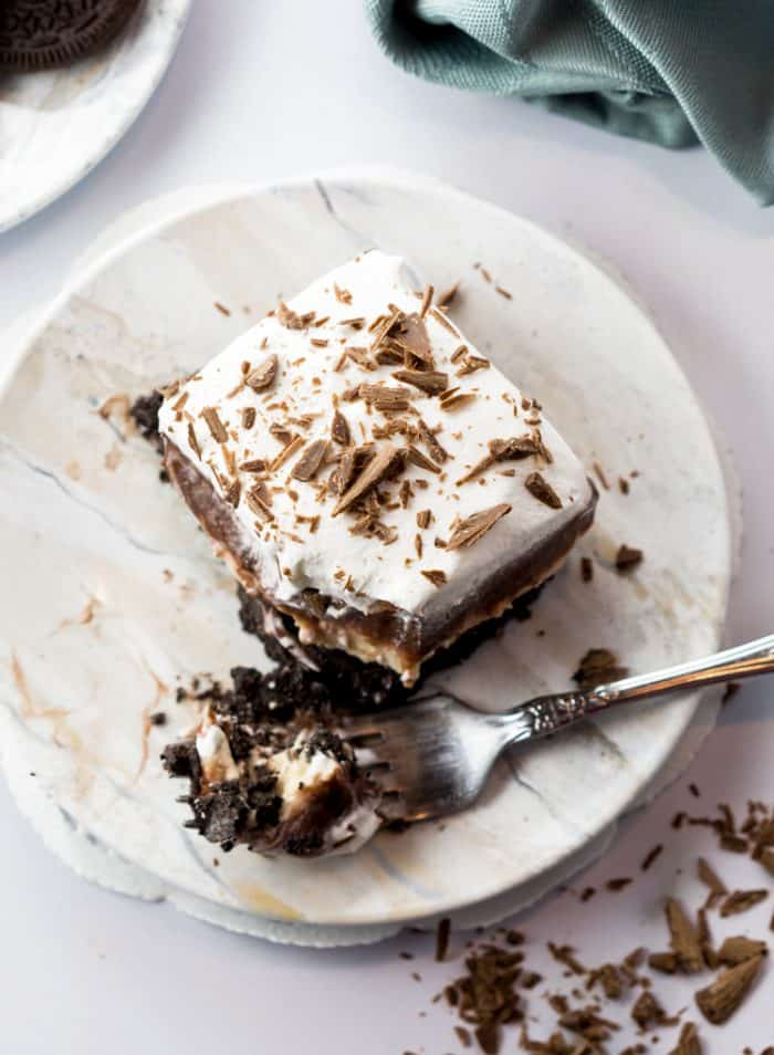Peanut Butter Pie topped with chocolate shavings on a white plate with a fork.