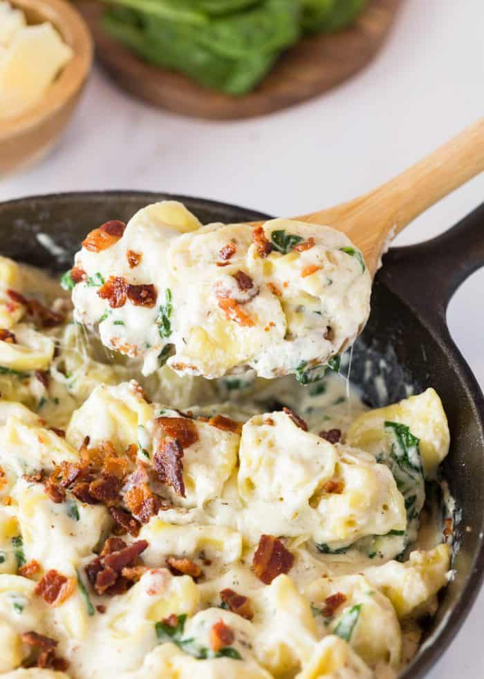 A cast iron skillet filled with tortellini in a cream sauce topped with bacon and a wooden spoon scooping some out.