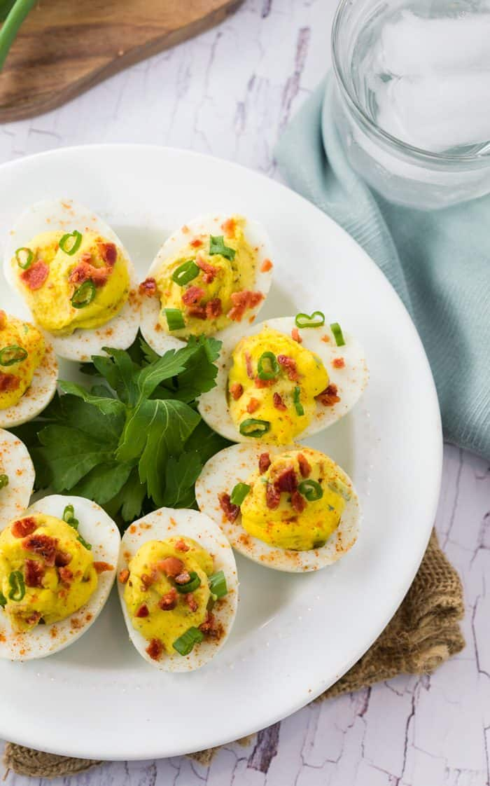 Deviled Eggs on a white plate topped with bacon and green onions.
