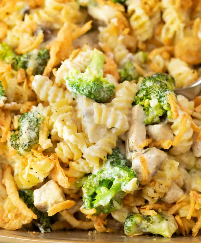 A close up view of spiral pasta noodles in a cheesy sauce with broccoli and chicken.