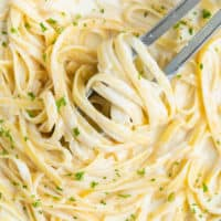 Overhead view of a pan filled with Creamy Fettuccine Alfredo with kitchen tongs.