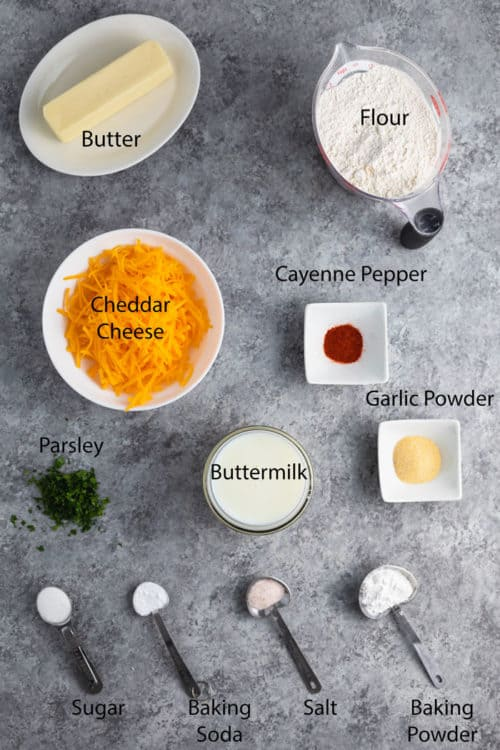 Overhead view of ingredients on a blue surface to make cheddar bay biscuits from scratch.