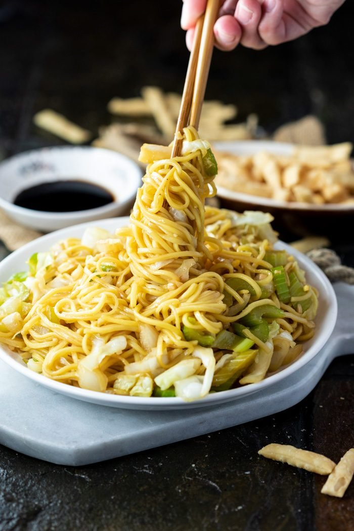 A white plate on a marble cutting board filled with chow mein and a hand holding chopsticks twisting up the noodles.