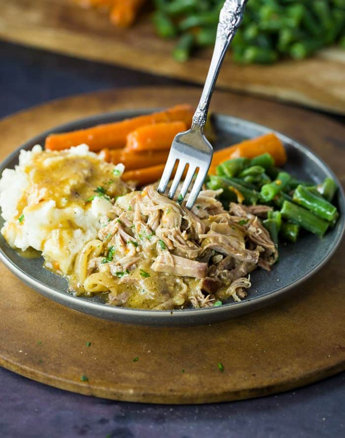 Shredded pork topped with parsley and gravy with a fork in it, with potatoes, carrots, and green beans in the background.