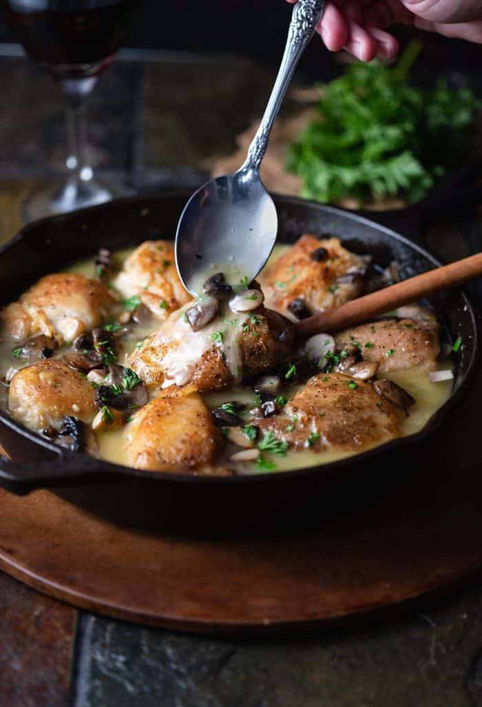 A cast iron skillet filled with golden chicken thighs with a spoon drizzling white wine sauce with mushrooms on top.