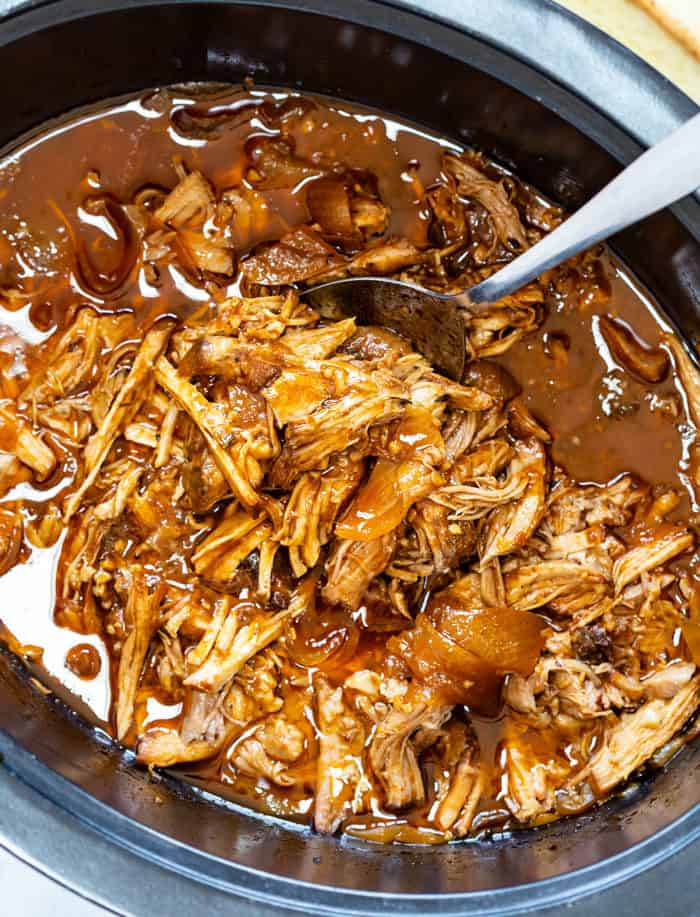 Pulled Pork in the Crock Pot with a Spoon scooping it up.