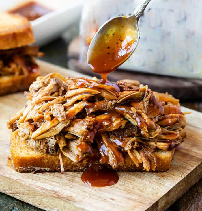 A spoon drizzling BBQ Sauce over pulled pork on a slice on bread.
